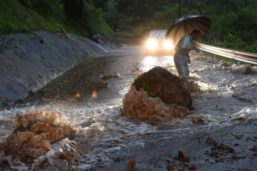 A flooded road with fallen rocks is pictured in Hita in Oita Prefecture, Japan, after torrential rain hits, on July 5, 2017.