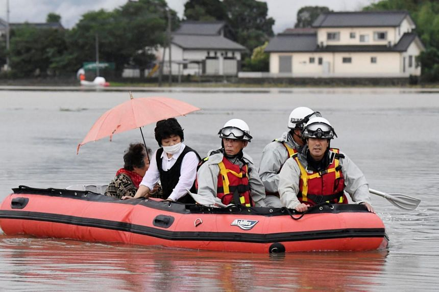 Local residents are rescued by firefighters after heavy rain hit the area in Asakura, Fukuoka Prefecture, on July 6, 2017.