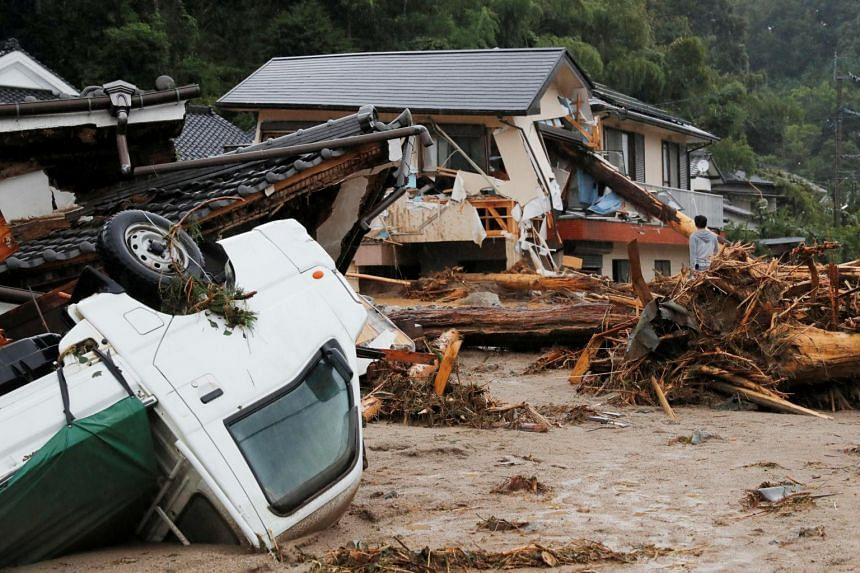 Houses and a vehicle are damaged by a swollen river after heavy rain hit the area in Asakura, Fukuoka Prefecture, Japan in this photo taken by Kyodo, on July 6, 2017.