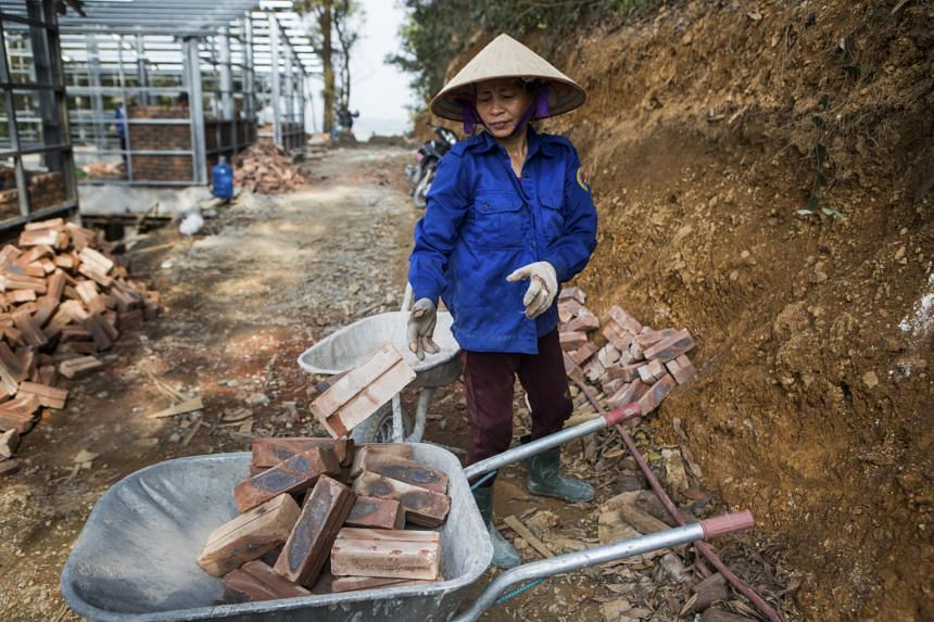 "A builder gathers bricks for construction of an ""S House,"" designed by architect Vo Trong Nghia, in Hanoi, April 20, 2017."