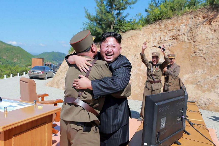 North Korean leader Kim Jong-Un (centre) celebrates the successful test-fire of the Hwasong-14.