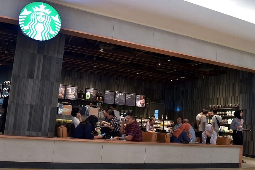 This photo taken on July 4, 2017 shows customers sitting inside a Starbucks cafe at a shopping mall in Jakarta.