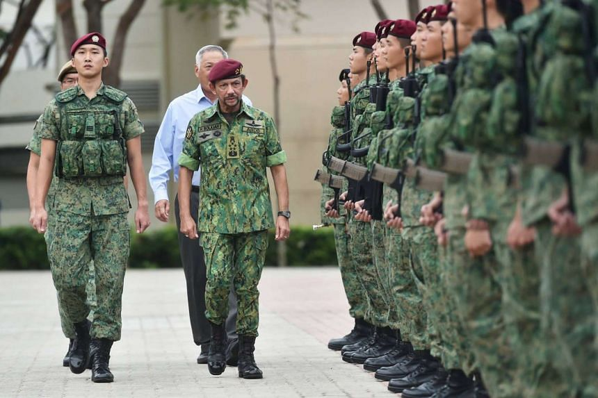 Sultan Hassanal Bolkiah of Brunei inspecting the Guard of Honour at Pasir Ris Camp, with Defence Minister Ng Eng Hen walking behind him, on July 6, 2017.
