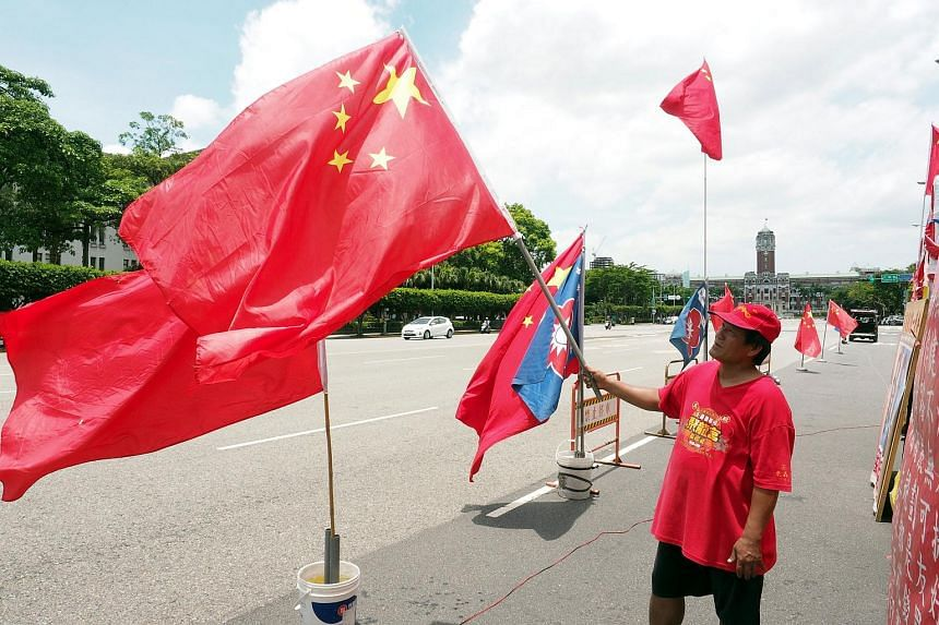 A member of a pro-China group displays China's national flag in front of the Presidential Office Building in Taipei, Taiwan on June 26, 2017.