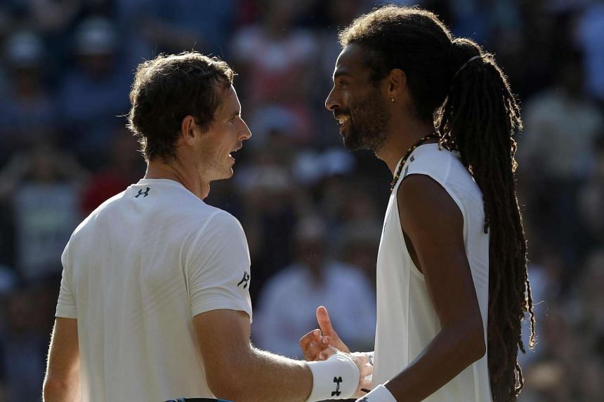 Murray (left) shakes hands with Brown after winning their second-round match.