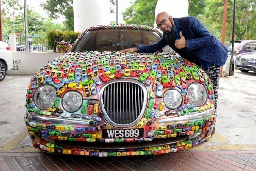 Datuk Seri Mahadi Badrul Zaman with his Jaguar that is covered in toy cars.