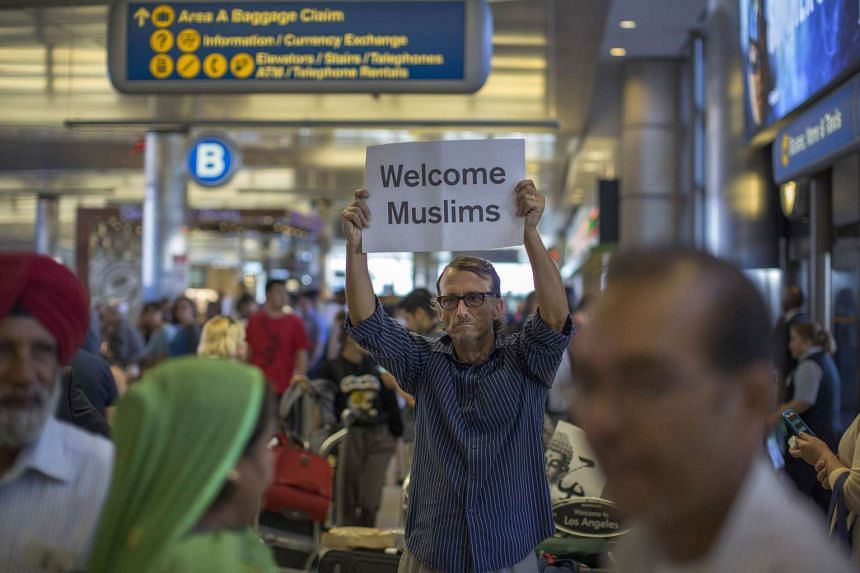 A man carries a welcome sign on the first day of the partial reinstatement of the Trump travel ban, June 29, 2017, in Los Angeles.