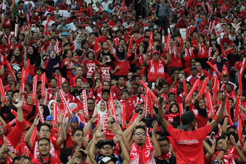 Singapore fans cheering on the Lions during a match against Malaysia at the National Stadium.