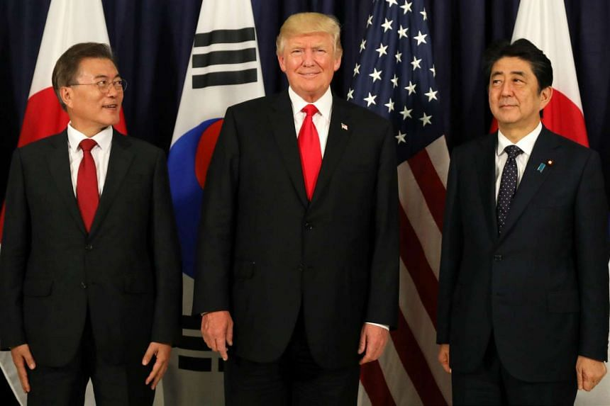 Donald Trump (centre) meets Moon Jae-In (left) and Shinzo Abe ahead of the G-20 leaders summit.