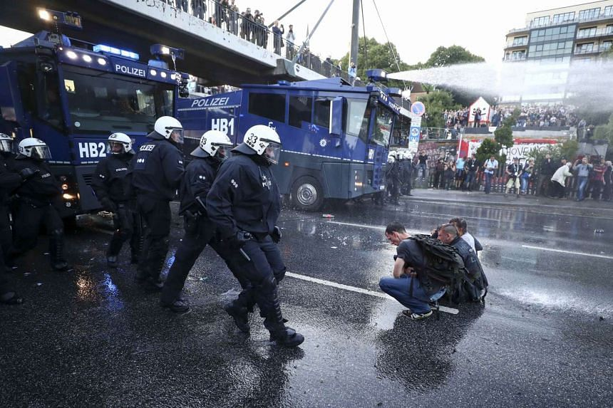 German riot police use water cannon against protesters.