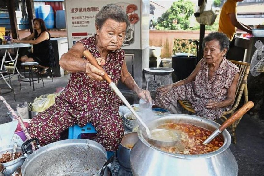 The Lim sisters preparing their famous curry mee for takeaway at their stall.