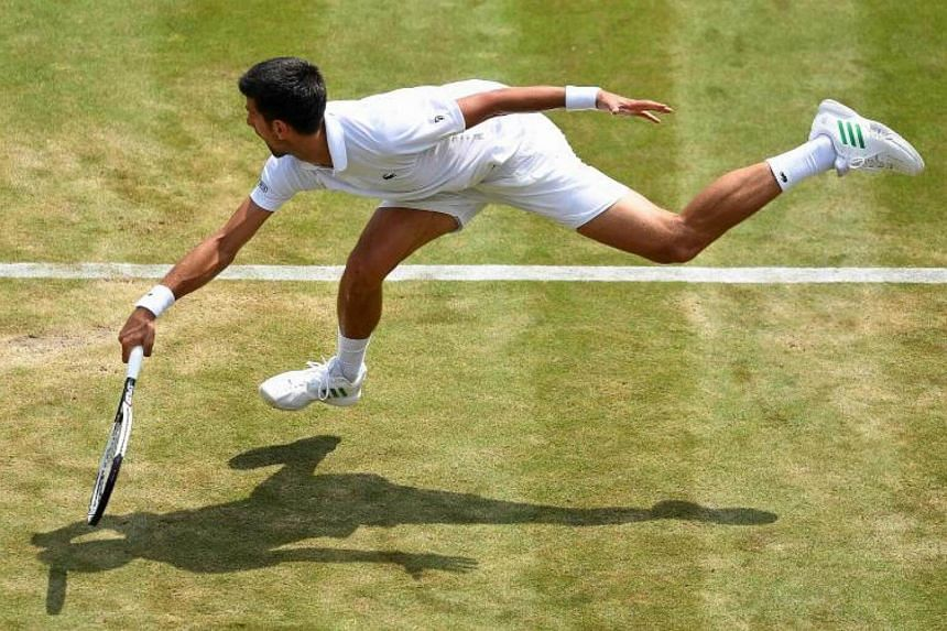 Serbia's Novak Djokovic dives in an attempt to return to Czech Republic's Adam Pavlasek during their men's singles second round match at The All England Lawn Tennis Club in southwest London, on July 6, 2017.