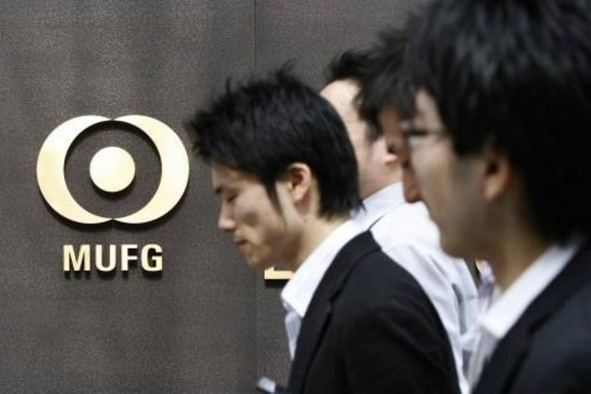Pedestrians walk past a logo of Mitsubishi UFJ Financial Group Inc. (MUFG) at the company headquarters in Tokyo.
