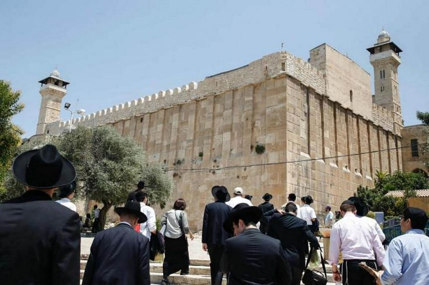Religious Jews and tourists walking towards the Cave of the Patriarchs, a holy shrine for Jews and Muslims, from the Israeli side in the heart of the divided city of Hebron in the southern West Bank on July 7, 2017.