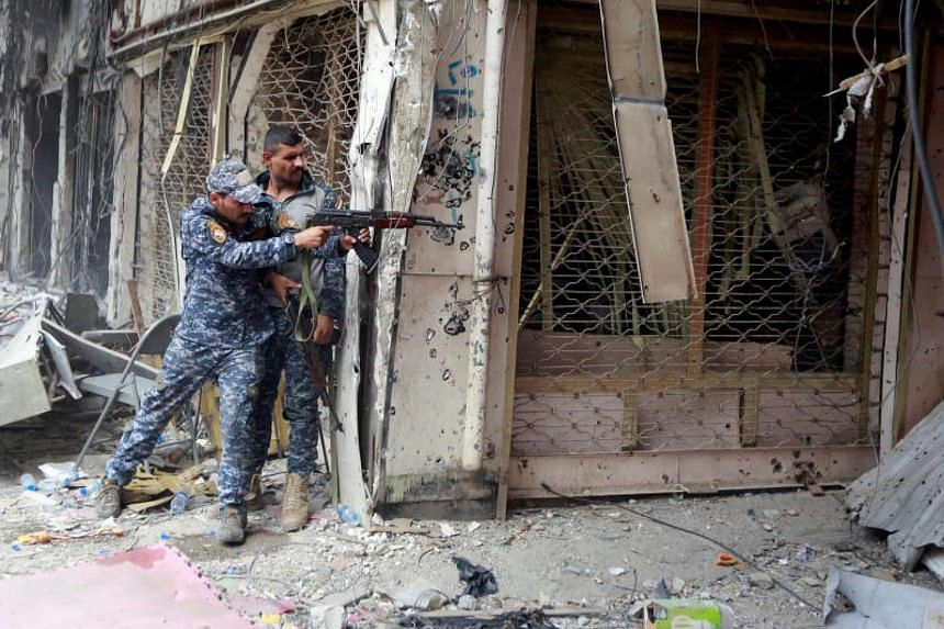 A member of the Iraqi Federal Police opens fire against Islamic State militants in the Old City of Mosul, Iraq on July 7, 2017.