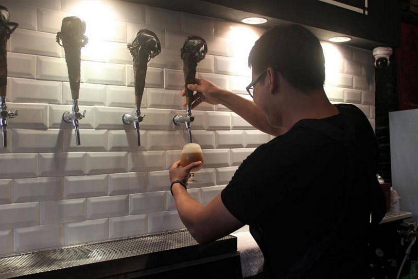 A staff draws beer from one of the six taps available at the GoldenCoins Taproom bar in Ekkamai, Bangkok.