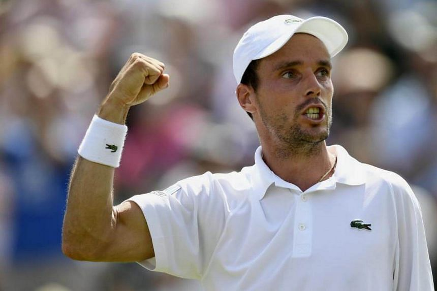 Roberto Bautista Agut of Spain celebrates winning against Kei Nishikori of Japan during their third round match for the Wimbledon Championships at the All England Lawn Tennis Club, in London, Britain, on July 7, 2017.