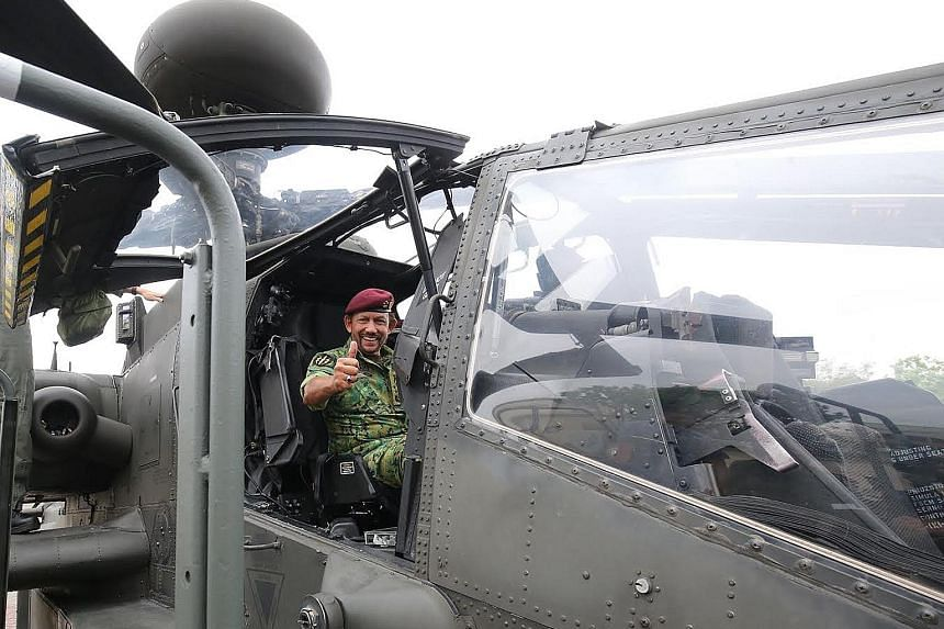 Sultan Hassanal Bolkiah in the cockpit of an Apache helicopter. He was taken on a tour of the army's Airborne-Trooper Training Facility and was later presented with the SAF's Honorary Advanced Military Freefall Wings to commemorate the event.