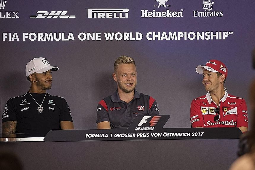 From left: Mercedes' Lewis Hamilton, Haas' Kevin Magnussen and Ferrari's Sebastian Vettel are all smiles at a drivers' press conference ahead of the Austrian Grand Prix this weekend.