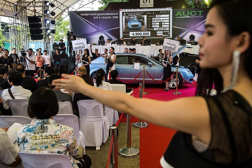 Yesterday, buyers raised bids for a variety of gleaming sports cars, including Ferraris and Aston Martins. Most of the vehicles had been confiscated because they were illegally smuggled, or the owners had tried to avoid paying the full import tax, wh