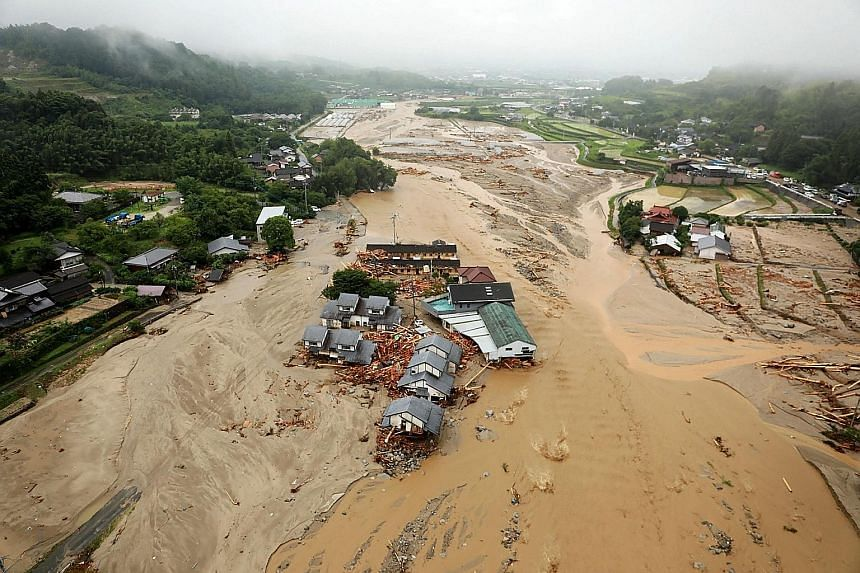Right: Asakura City in Fukuoka prefecture is among the hardest-hit areas, with footage showing floodwaters surging through the streets yesterday. Above: These soldiers rescuing an elderly man in Asakura were among thousands of police officers and tro