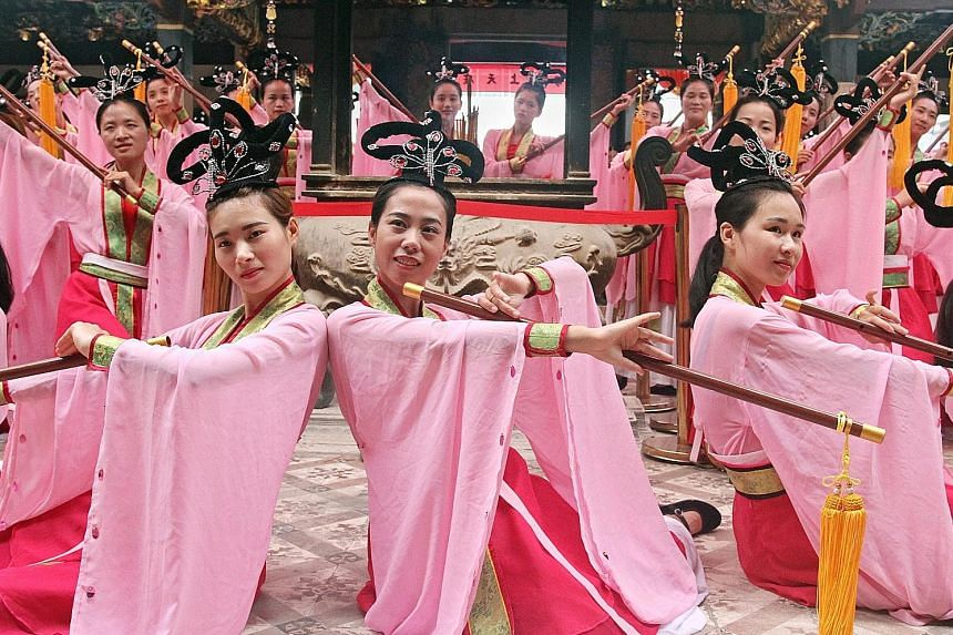 Right: Dancers from Meizhou performing as part of a ceremony in honour of Mazu. Above: Thousands of devotees were at Thian Hock Keng temple yesterday to see the statue.