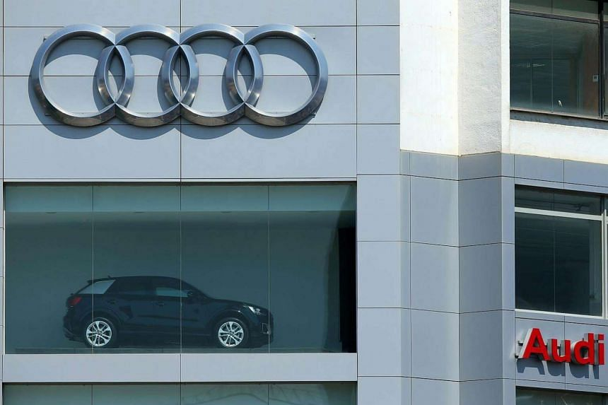 An Audi Q2 car is shown under a giant logo at a dealership in Barcelona.