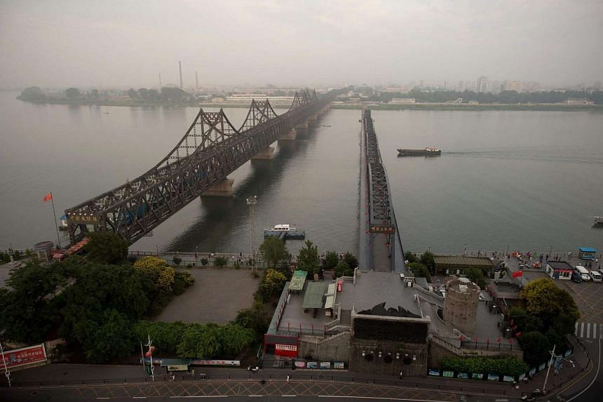 Dusk settles over the Friendship Bridge on the Yalu River connecting the North Korean town of Sinuiju and China's border city of Dandong on July 5, 2017.