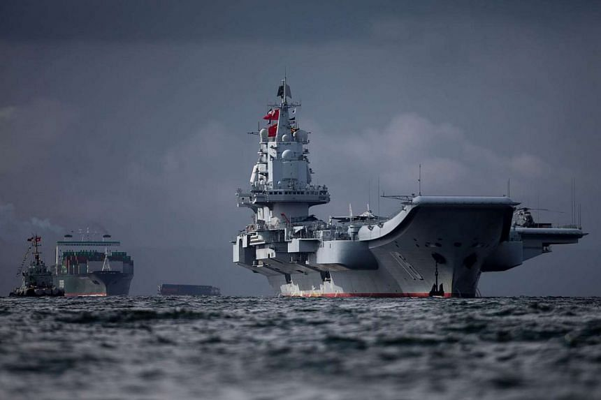 The Liaoning (right), the first aircraft carrier commissioned into China's military, arrives in Hong Kong, on July 7, 2017.