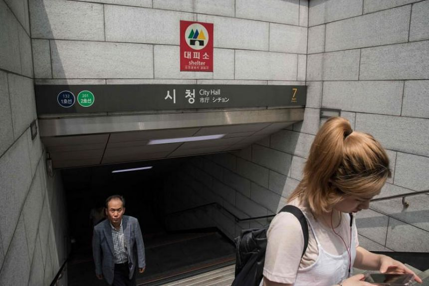 """A """"shelter"""" sign is displayed at the entrance to a subway station in Seoul on July 5, 2017."""