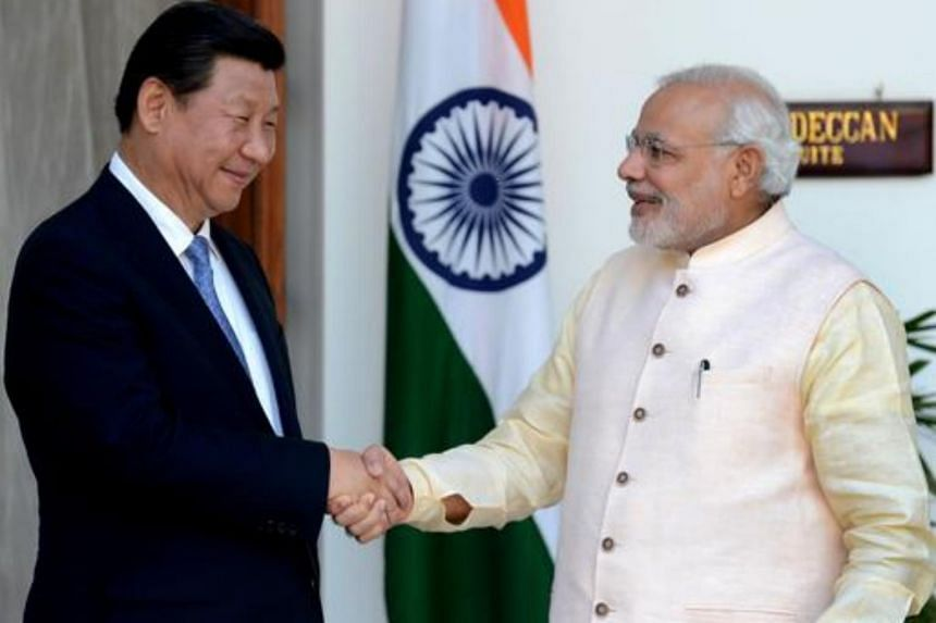Indian Prime Minister Narendra Modi (right) shakes hands with Chinese President Xi Jinping during a meeting in New Delhi, on Sept 18, 2014.