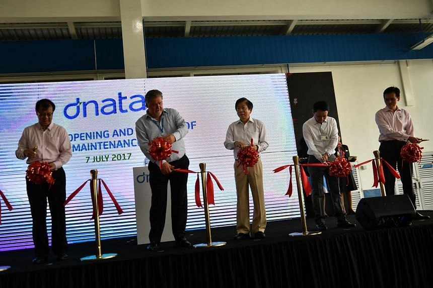 Coordinating Minister for Infrastructure & Minister for Transport Mr Khaw Boon Wan (centre) cutting the ribbon to officially open and launch dnata's new maintenance base.