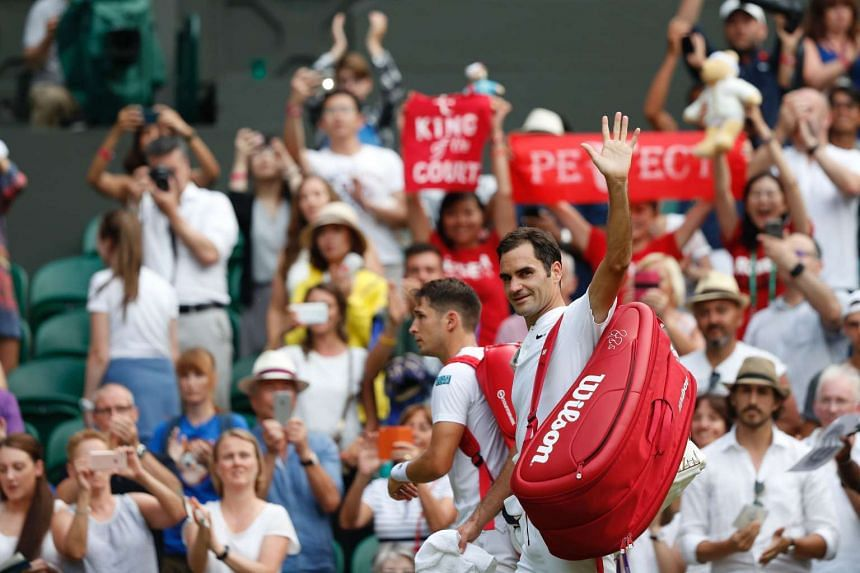 Federer (R) waves as he leaves the court.
