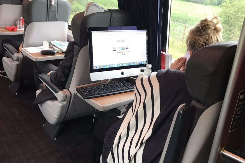 The woman set up her iMac desktop on the table at her seat while on a train travelling to London.
