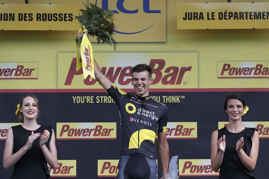 Calmejane of France celebrates on the podium after winning the eighth stage.