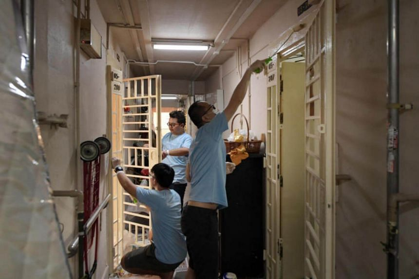 Volunteers paint the gates of residents in Chai Chee Avenue.