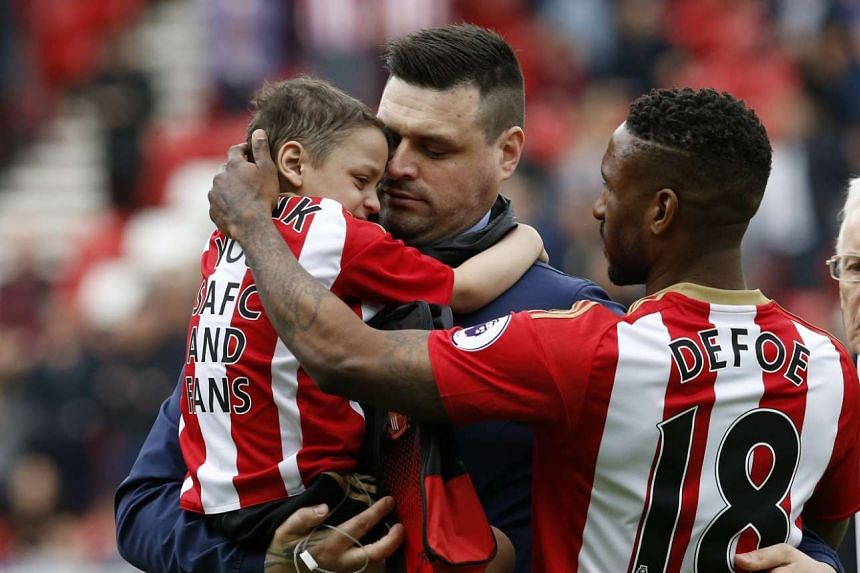 Defoe passes Bradley to his father after walking out with him before a match.