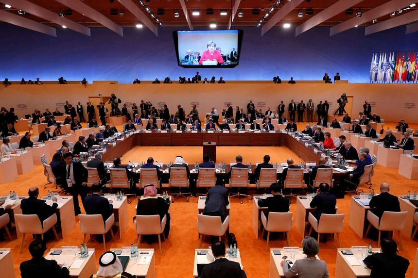 General view of the discussion table while German Chancellor Angela Merkel is seen on the screen above during the G20 leaders summit in Hamburg, Germany July 7, 2017.