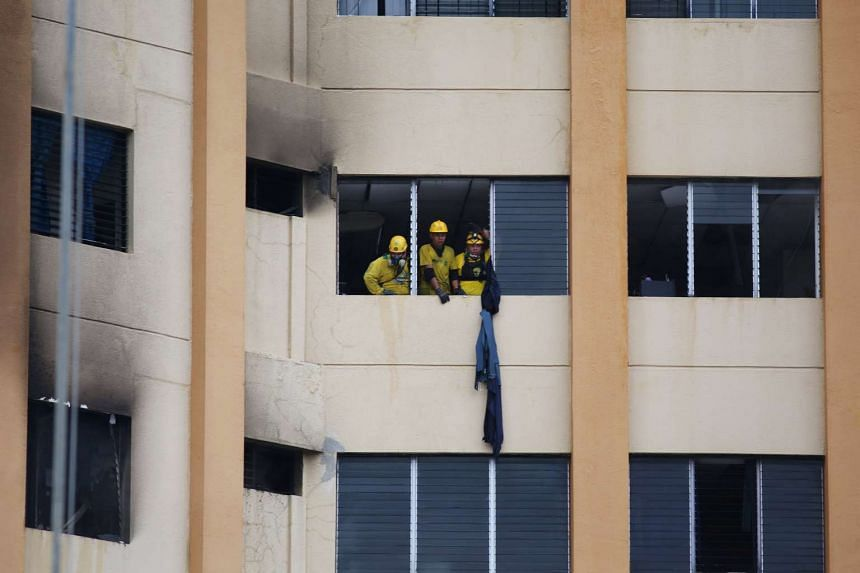 Rescuers working at the ministry of treasury building during a blaze in San Salvador, El Salvador, on July 7, 2017.