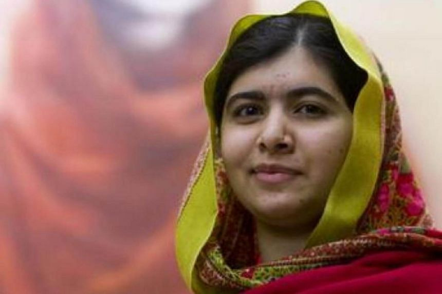 Malala Yousafzai poses for photographers in front of Malala 2015, a new official portrait of Malala in Birmingham, central England, on Nov 29, 2015.