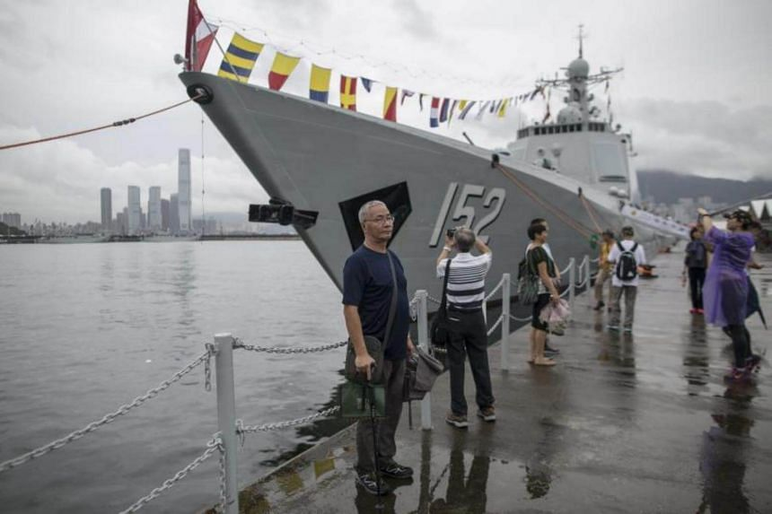Members of the public pose for photographs in front of a People's Liberation Army (PLA) ship during an open day at the PLA navy base in Hong Kong, China, on July 8, 2017.