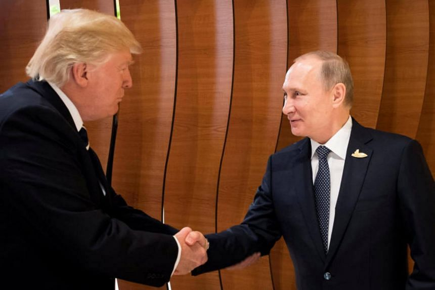 US President Donald Trump and Russia's President Vladimir Putin shake hands during the G20 Summit on July 7, 2017.