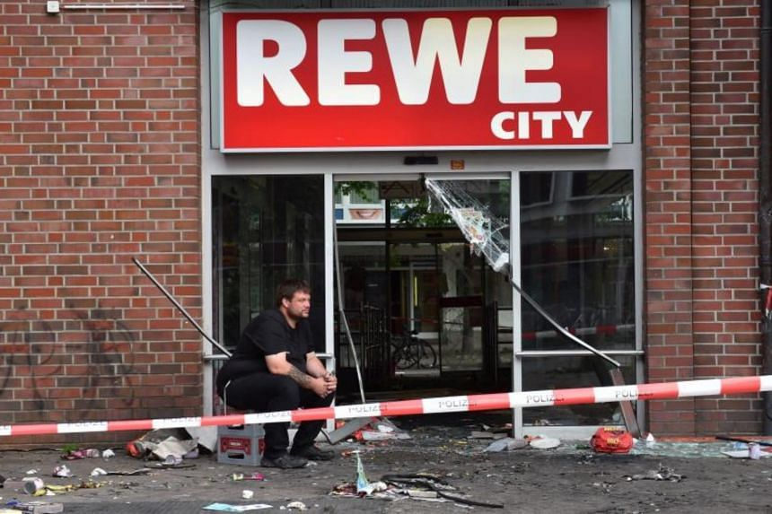 A man sits in front of a destroyed Rewe City supermarket after riots in Hamburg's Schanzenviertel district on July 8, 2017 in Hamburg, northern Germany, where leaders of the world's top economies gather for a G20 summit.
