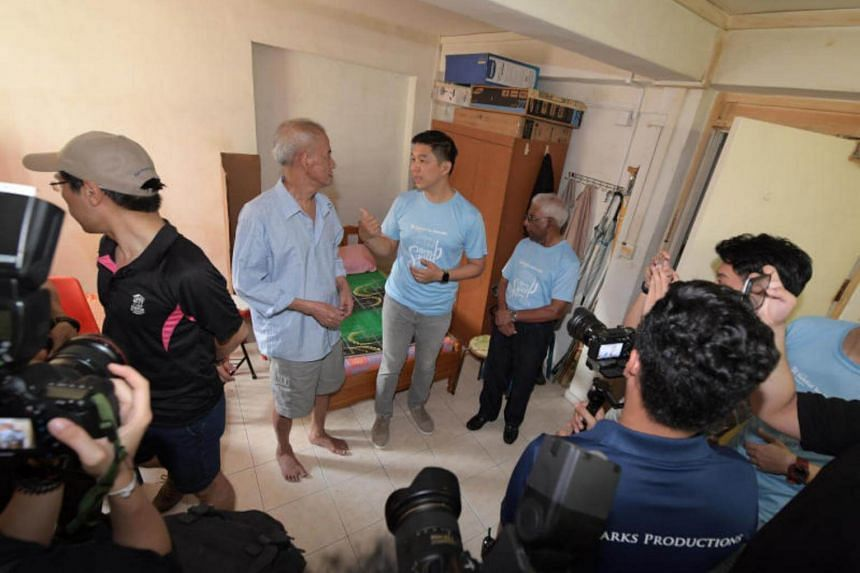 Minister Tan Chuan Jin (centre) speaks with resident Low Chin Hee (centre, left), 66, a former painter, in his Chai Chee Avenue apartment.