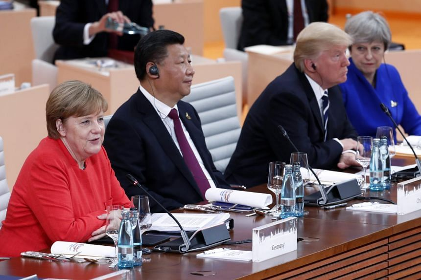 German Chancellor Angela Merkel (left) sitting next to Chinese President Xi Jinping (second, left), US President Donald Trump (second, right) and British PM Theresa May (right) at the beginning of the plenary session of the G20 summit in Hamburg, Ger