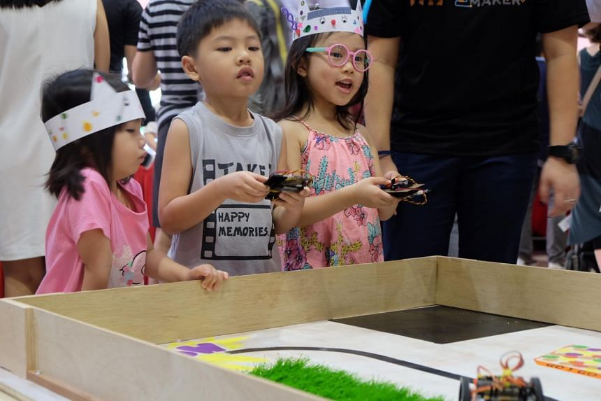 Children playing with cars powered by the micro:bit microcontroller. The first Digital Garage at Tanjong Pagar CC will hold workshops on how to code this device.