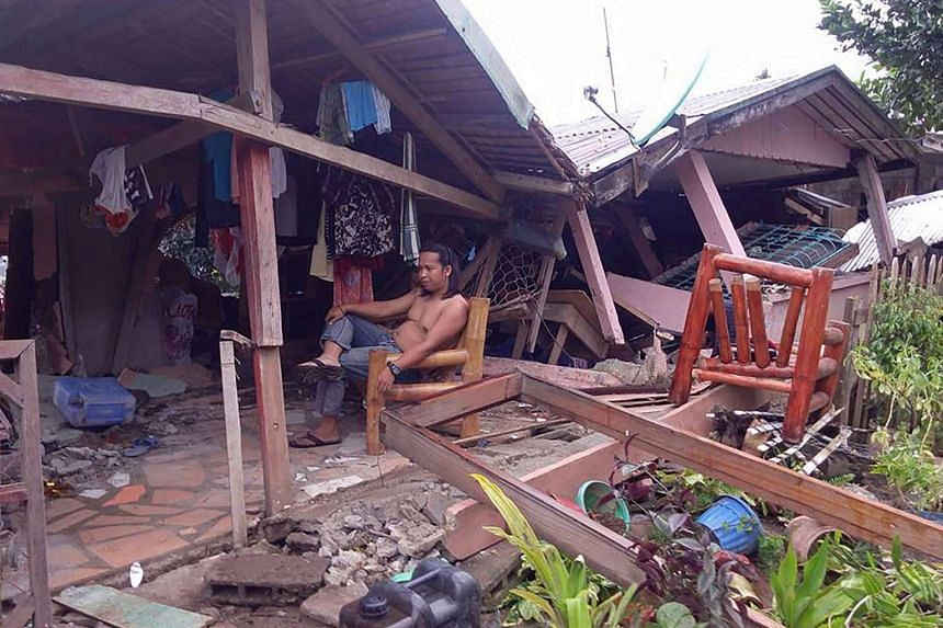 A resident rests at his collapsed house a day after a 6.5 magnitude earthquake hit the town of Tongonan, Leyte province, central Philippines on July 7, 2017.