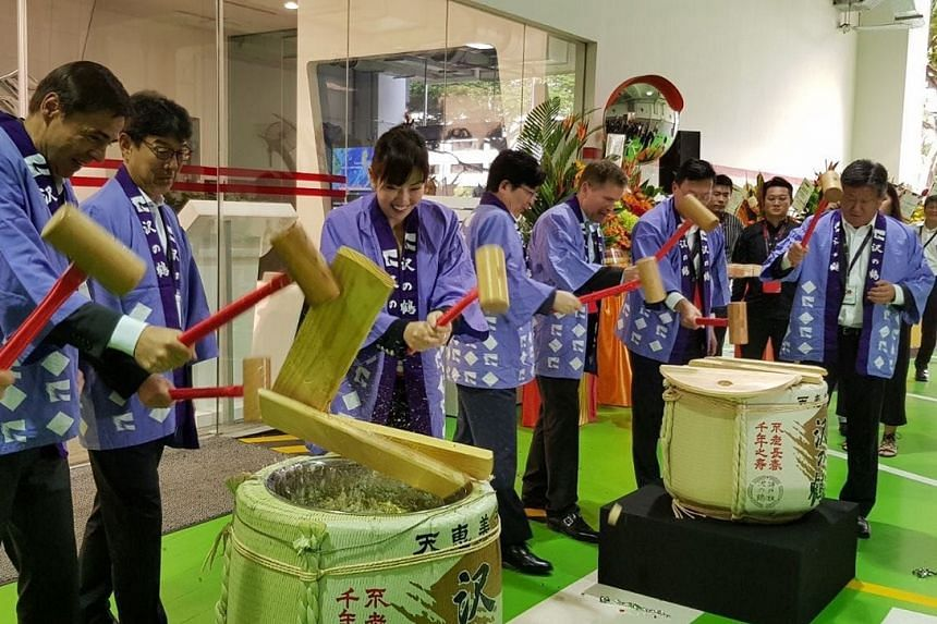 Inchcape opened its 10-storey integrated complex in Pandan Crescent on Thursday. Mr Stefan Bomhard, chief executive officer, Inchcape (second from far left) at the sake cask breaking ceremony.