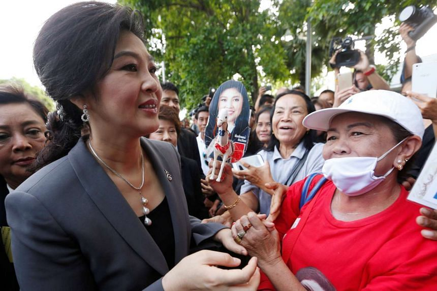 Ousted Thai prime minister Yingluck Shinawatra greeting supporters as she arrives at a Bangkok court yesterday for an ongoing trial that looks into a controversial rice subsidy scheme during her administration.