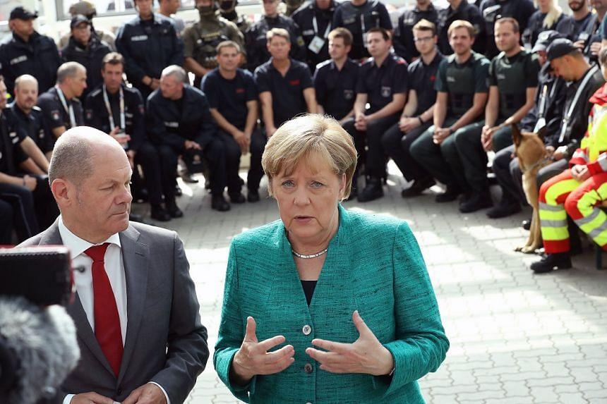 Merkel (centre) thanks members of German law enforcement and emergency services at the conclusion of the G-20.